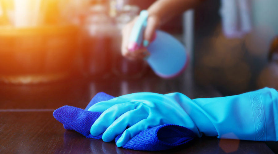 hand in blue rubber glove holding blue microfiber cleaning cloth and spray bottle with sterilizing solution make cleaning and disinfection for good hygiene
